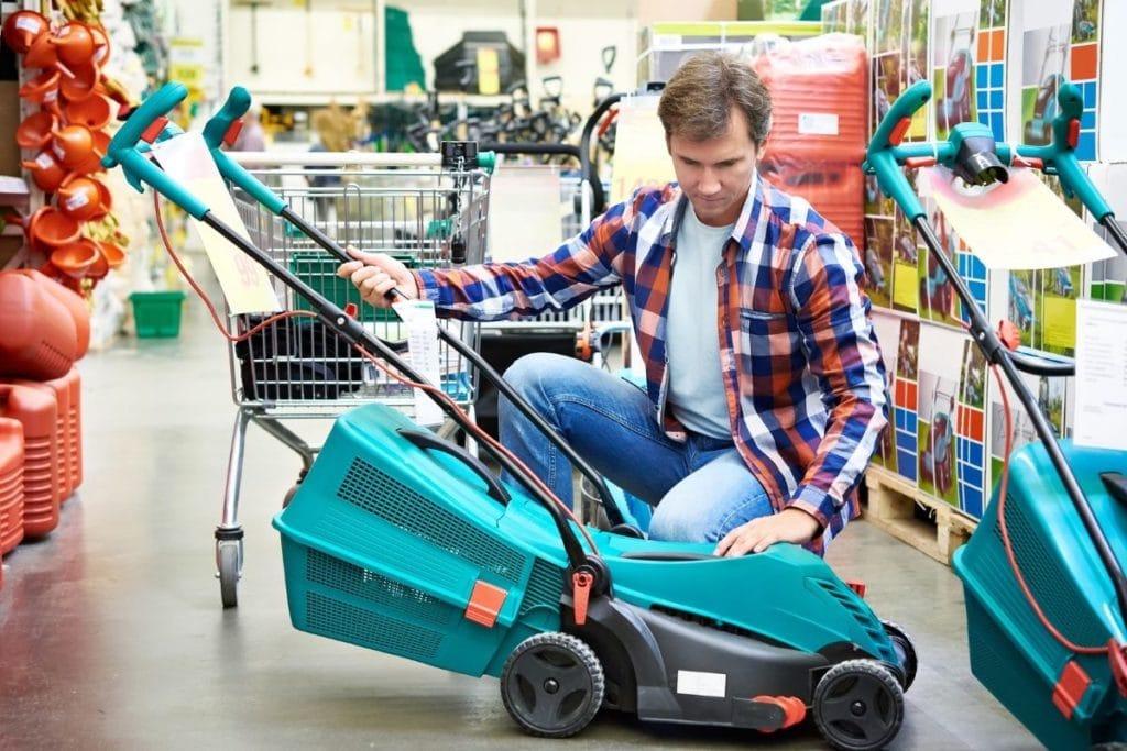Man Choosing one of the Best Self-Propelled Lawn Mowers