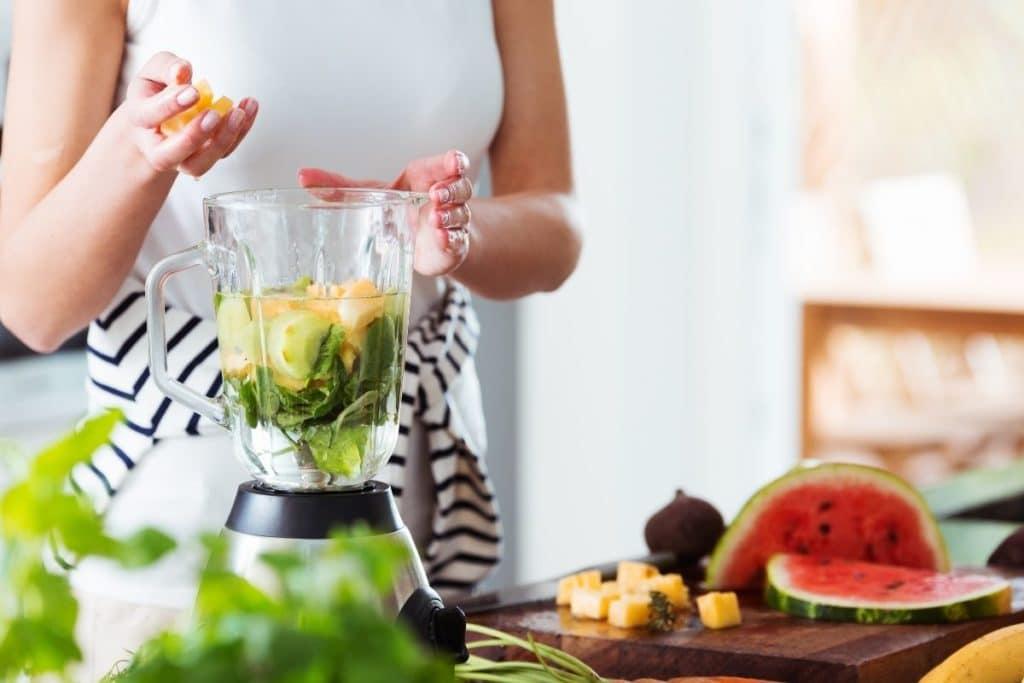 Woman using blender to make an energizing drink Food processors vs blenders