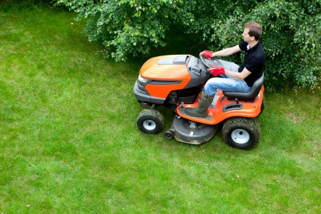 Man on Orange Riding Lawn Mower