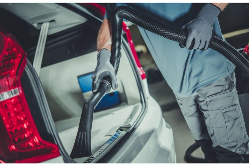 Using a canister vacuum cleaner to clear out the trunk of a car